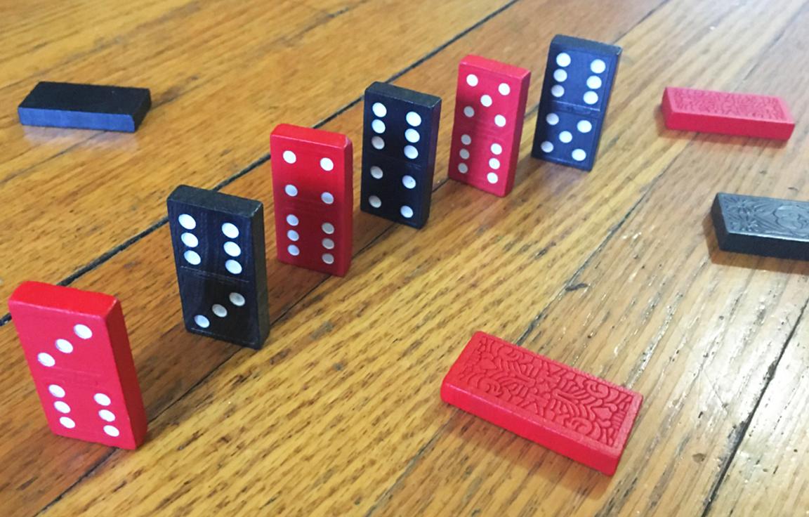 6 dominós parados. 4 dominós más están bocabajo (2 rojos y 2 negros). Los dominós que están parados son rojo, negro, rojo, negro, rojo, negro. Cada dominó rojo parado muestra 6 puntos en la parte de abajo. Cada dominó negro parado muestra 6 puntos en la parte de arriba. Cada uno de los primeros dos dominós parados tienen 9 puntos en total. Los segundos 2 dominós parados muestran, cada uno, 10 puntos en total. Cada uno de los últimos dos dominós parados muestra 11 puntos en total.