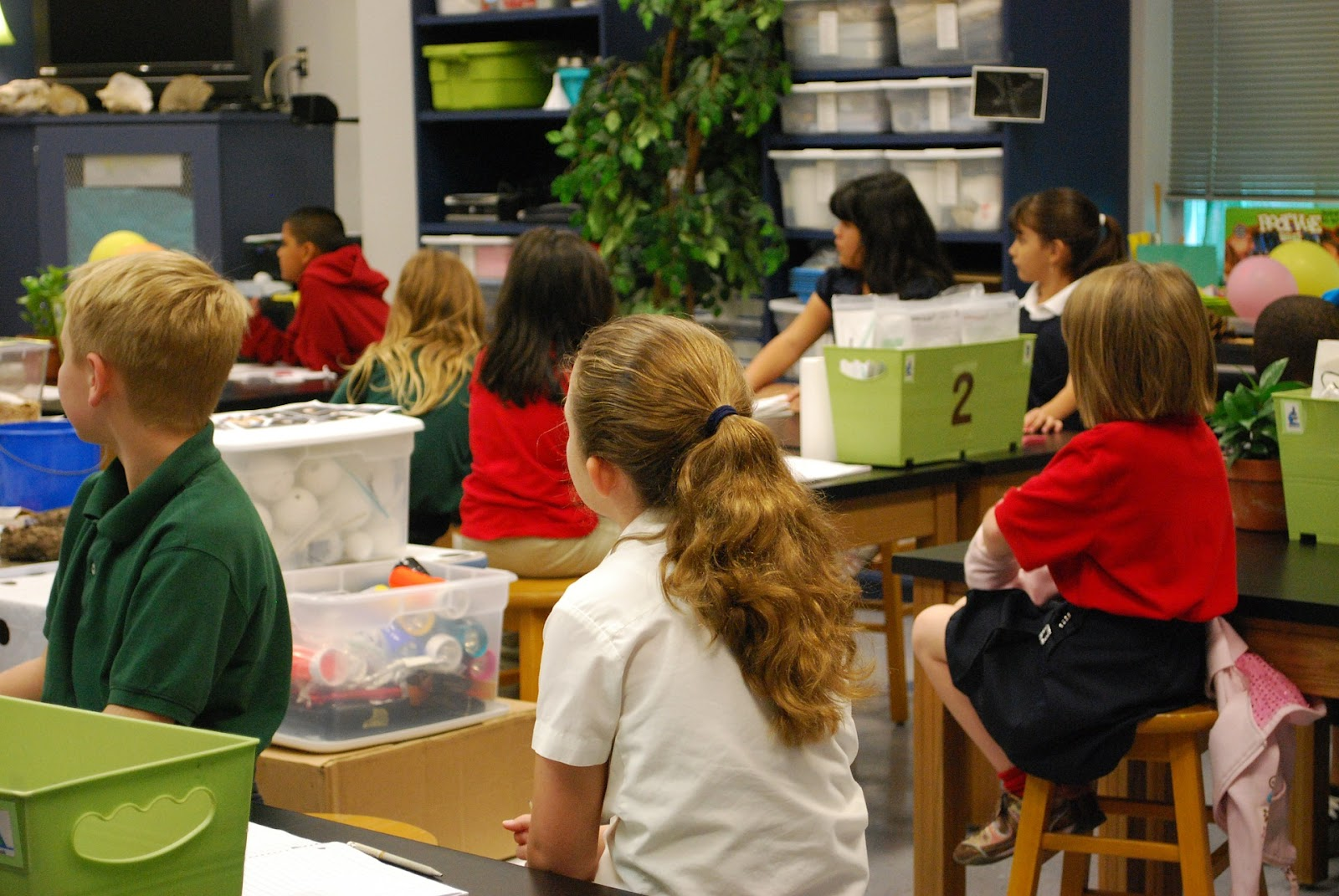 Students sit at tables in a classroom. There are numbered bins on some tables, and clear plastic bins on others. The bins are full of different types of STEM supplies. We can see styrofoam balls and colored cylinders in some of the bins.