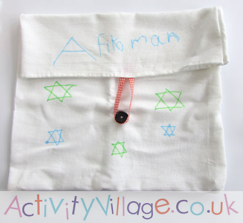 afikomen bag made from a tea towel, ribbon, and a button decorated by a child
