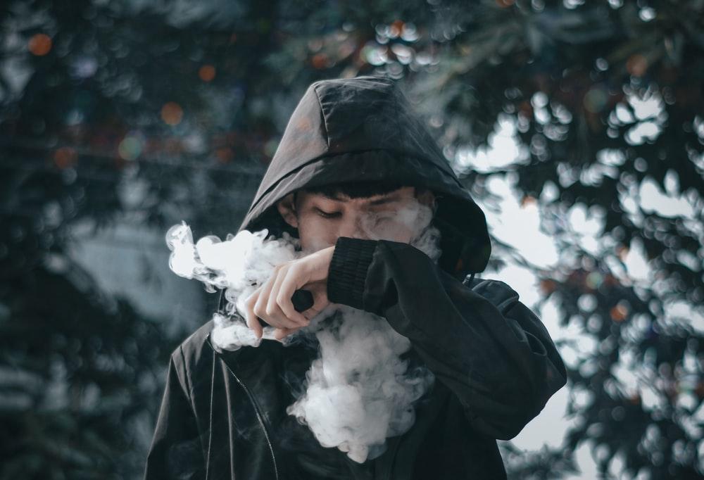 man in black hoodie holding white flower