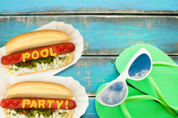dressed hot dogs spelling 'pool party' in condiments next to flip flops and sunglasses