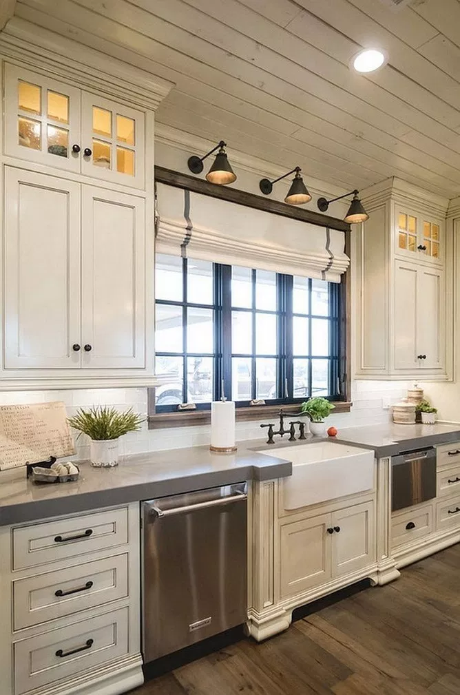 Modern rustic kitchen featuring antique white cabinets with black hardware. Black pendant lights highlight a large window over the farmhouse sink.