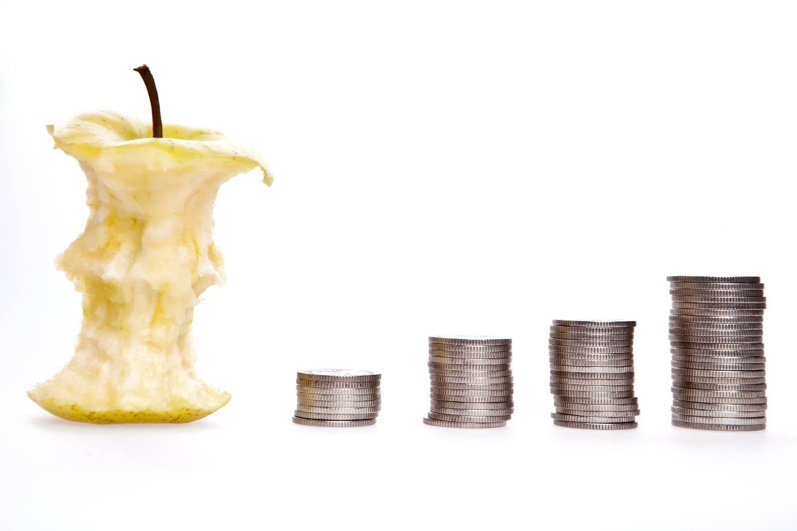 An apple core sits beside four stacks of coins, increasing in height.