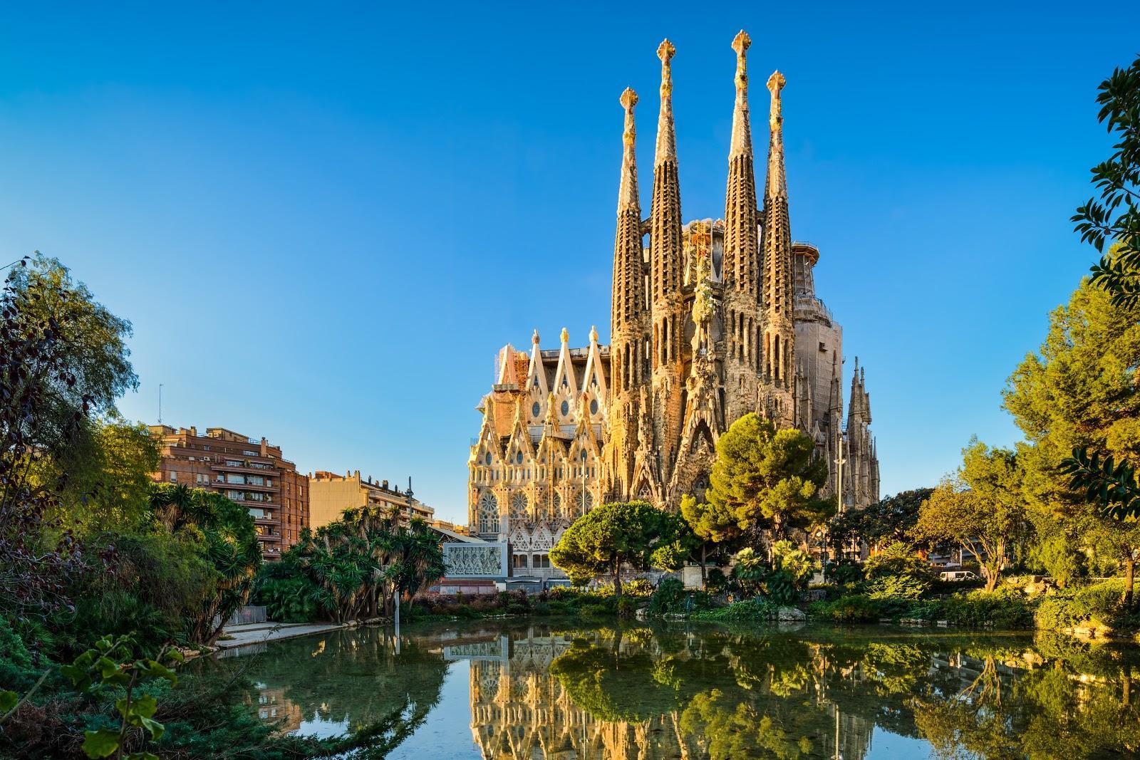 An exterior shot of the Sagrada Famila reflecting off a pond.