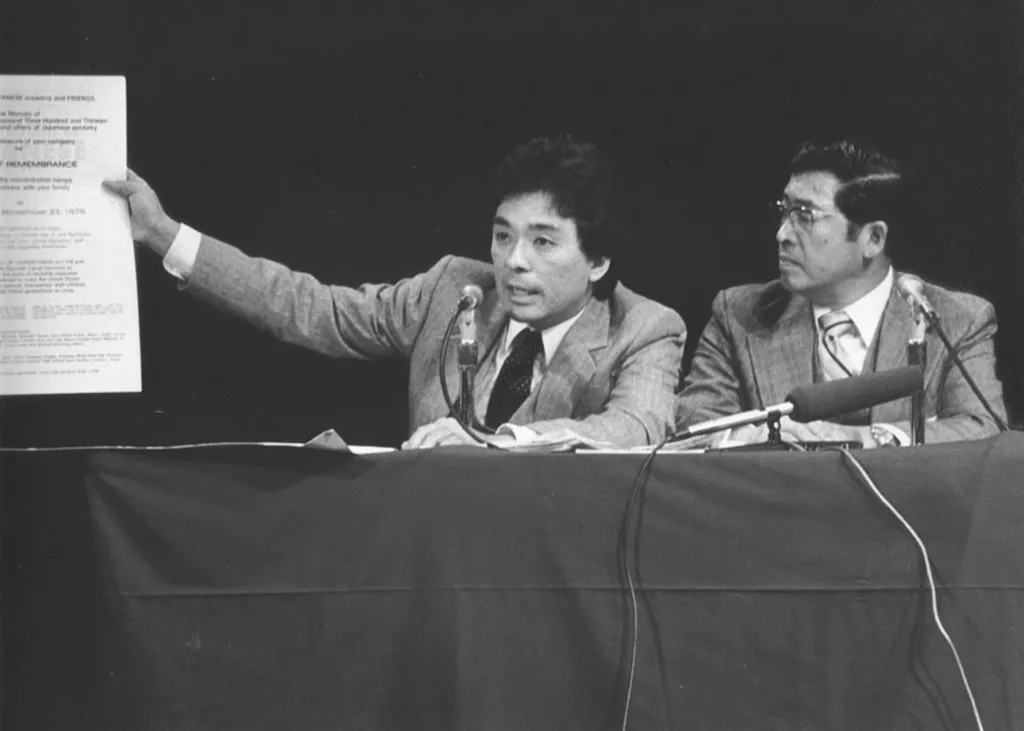 Frank Abe testifying at a Seattle redress hearing. He is holding up a poster from the first Day of Remembrance, which he helped organize in 1978.