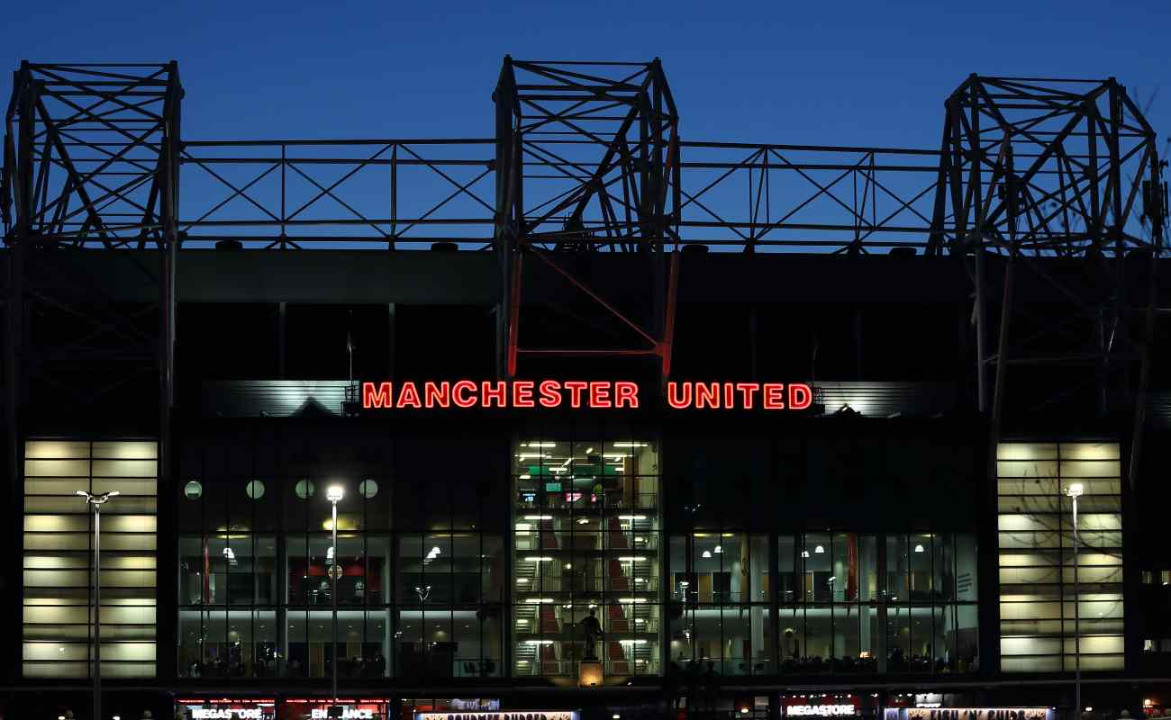 A red Manchester United sign lit up at the entrance of Old Trafford Stadium.