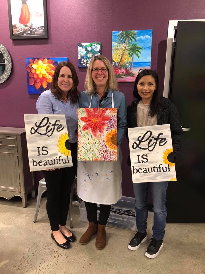 "women holding ""Life is Beautiful"" paintings"