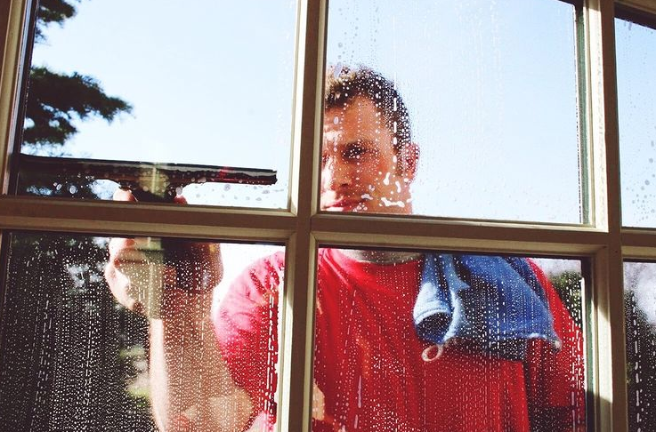 A man squeegeeing a window