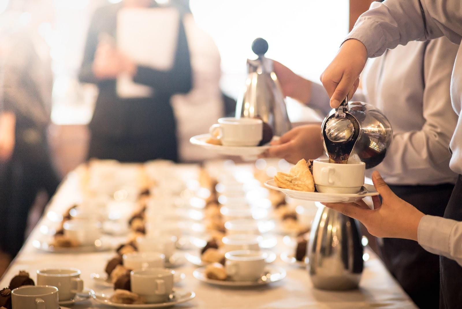 Pessoas servindo café e chá em um coffee break corporativo