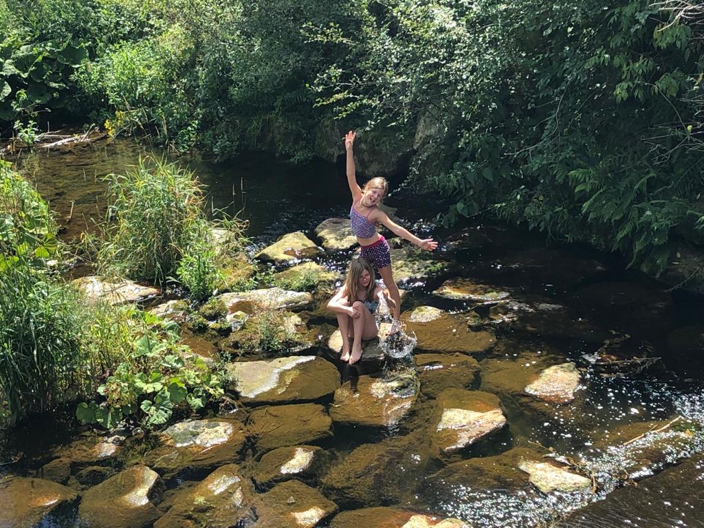 zwei Kinder stehen im seichten Flussbett