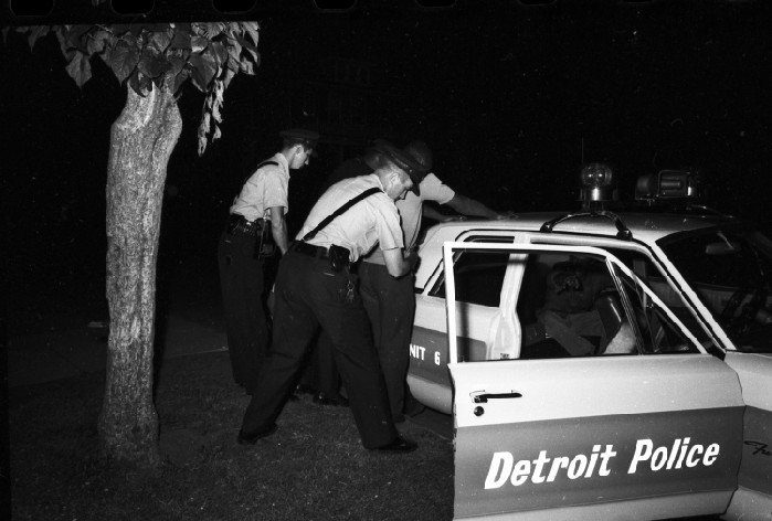 An old photo of Detroit police frisking a man