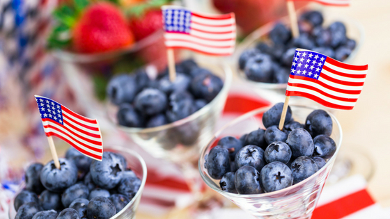 Blueberry patriotic desserts pictured, with miniature US flags stuck into cups of berries.