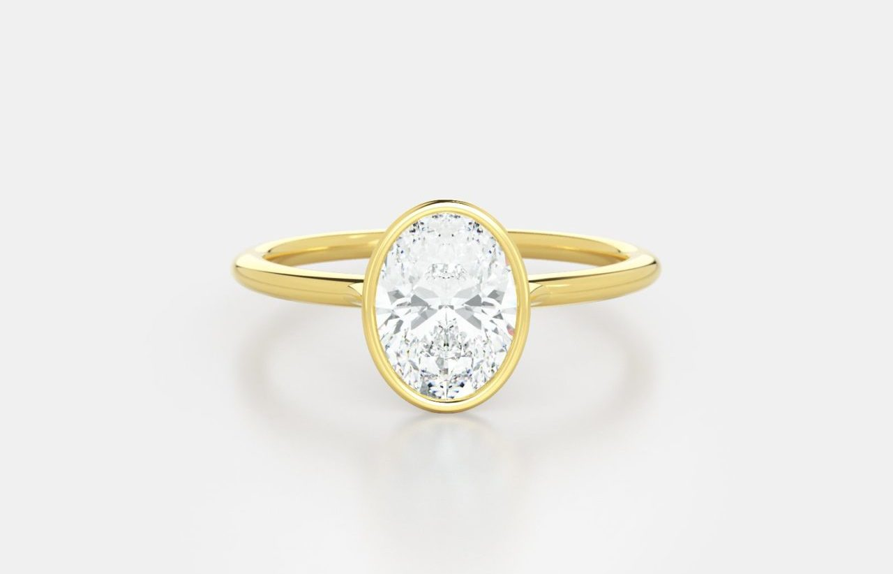Oval bezel solitaire in 18K yellow gold