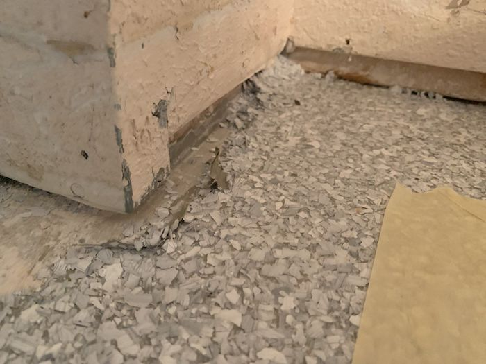 A close up of an old garage floor coating that has vinyl chips light grey colors and is peeling up around the walls.