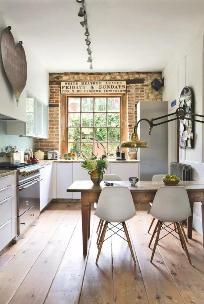 industrial rustic farmhouse kitchen with exposed brick wall, simple white cabinets, vintage wood table, simple white chairs and wood flooring