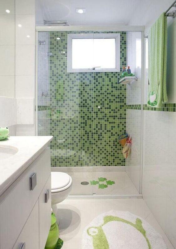 Banheiro com paredes, piso, armários e louças na cor branca, parede dentro do box com pastilhas verde e pastilhas em formato de faixa horizontal detalhando o ambiente