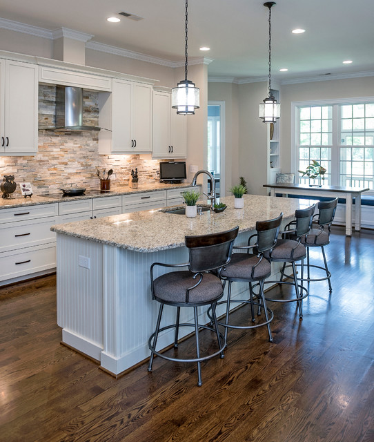 contemporary kitchen with white paneled island, white shaker cabinets, matte black hardware, natural stacked stone backsplash and under cabinet lighting