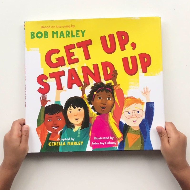 Book cover of Get Up, Stand Up by Bob Marley and Cedella Marley; children's hands holding the book, four cartoon children raising their hands
