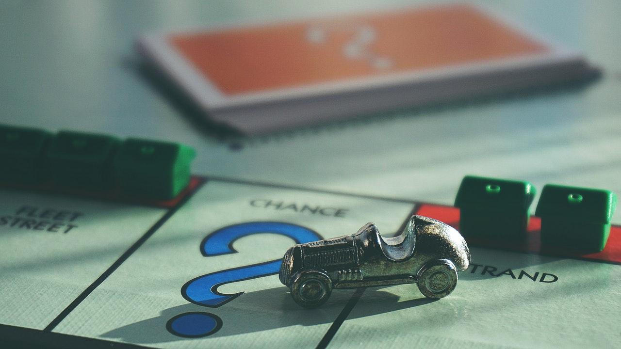 Plansza Monopoly z kartami i domkami obok pola na kartę szansy