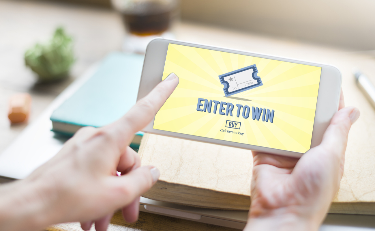 """Someone holding a mobile phone with the inscription """"Enter to Win"""""""