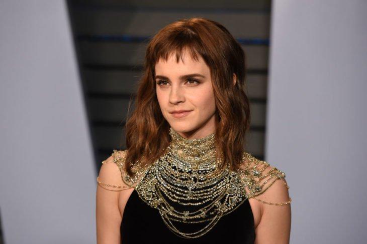 Emma Watson usando vestido negro con collar grande y pedrería