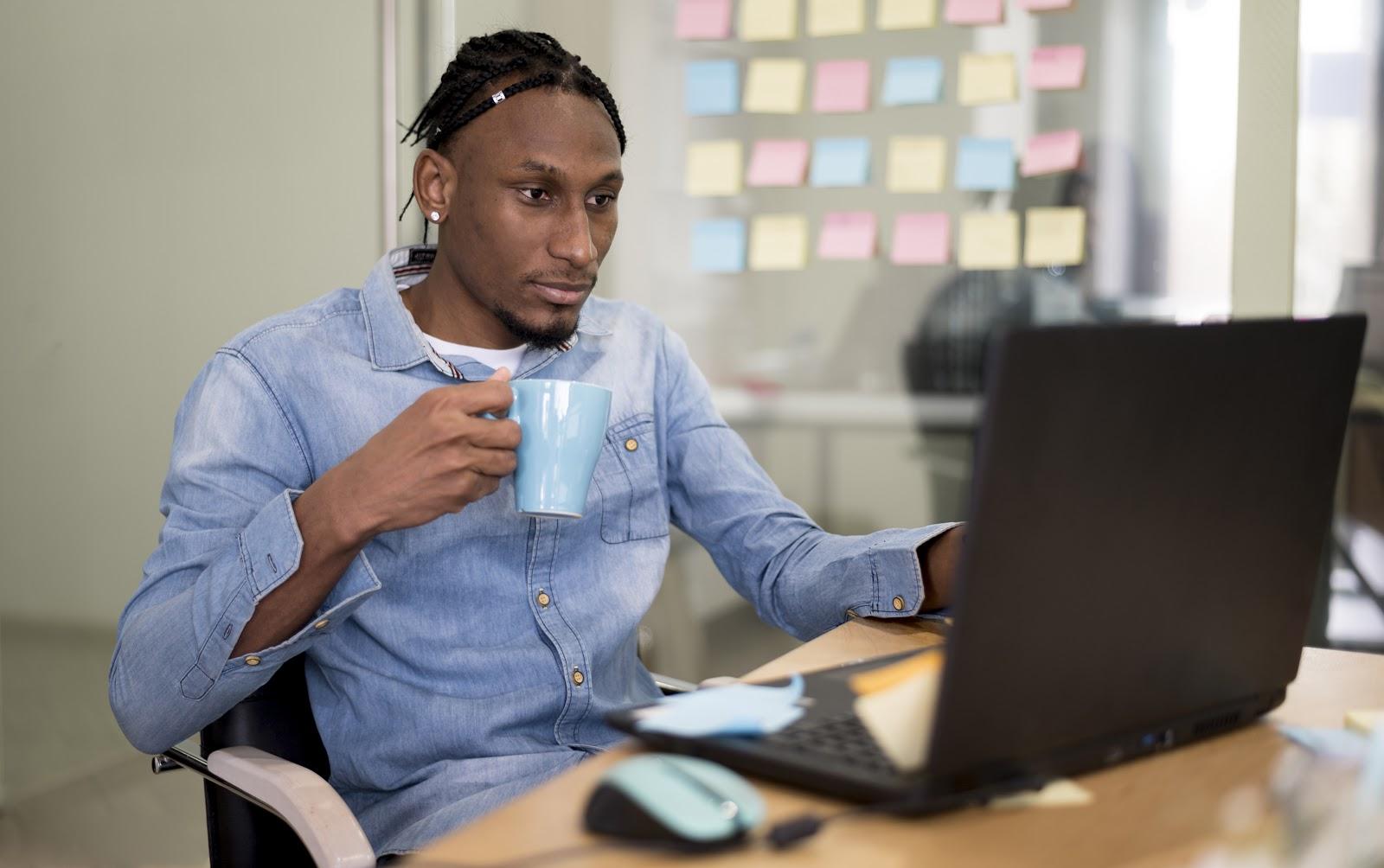 Imagem de um homem jovem segurando uma xícara e mexendo em seu notebook em um escritório, ilustrando a facilidade de trabalhar com metodologias ágeis.