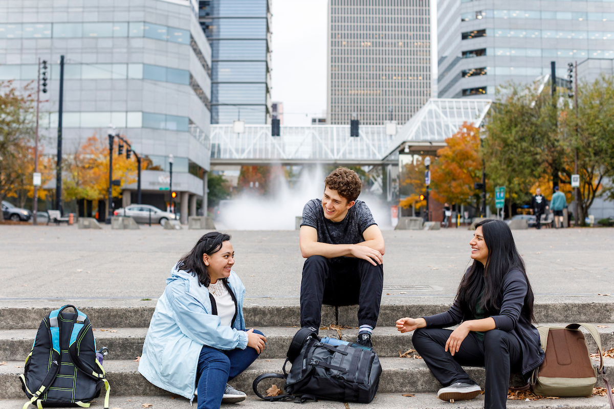 Three students sit outside near a fountain