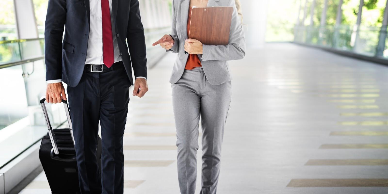 Homem e mulher com roupa formal indo para uma viagem de negócios