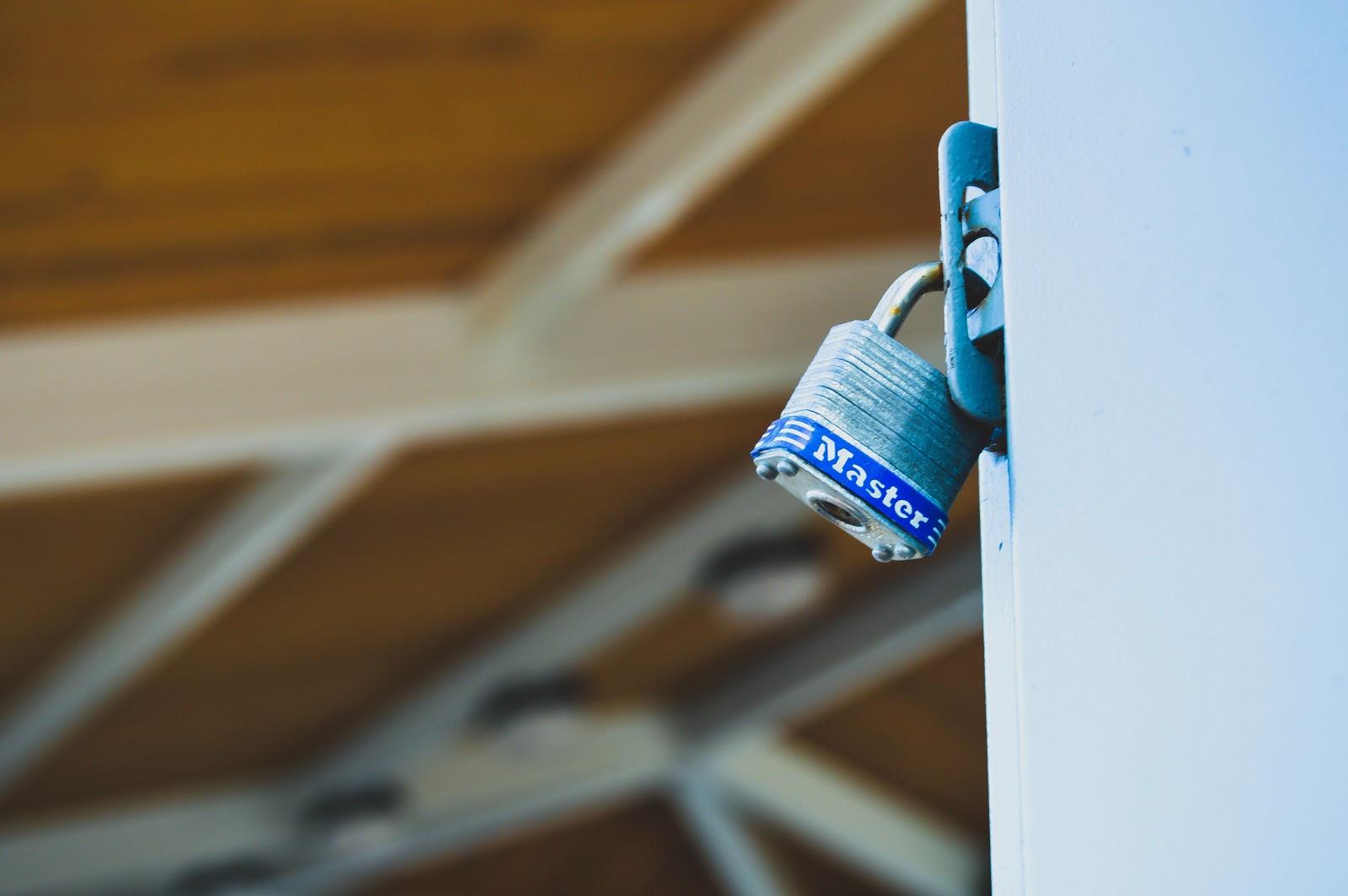 A metal lock is shut on a large door