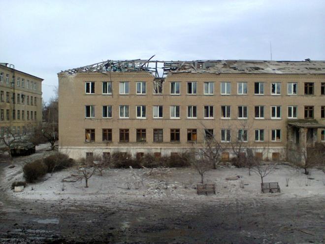 Один із корпусів школи-інтернату Вуглегірська після обстрілів. Український прапор на бронетранспортері ще цілий. Зона АТО, січень 2015 р