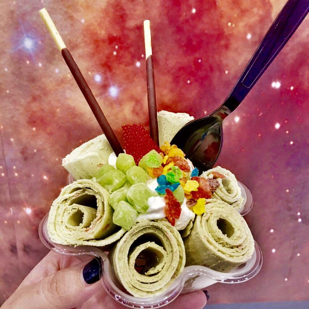 Rolled ice cream from Space Roll in front of a nebula wall