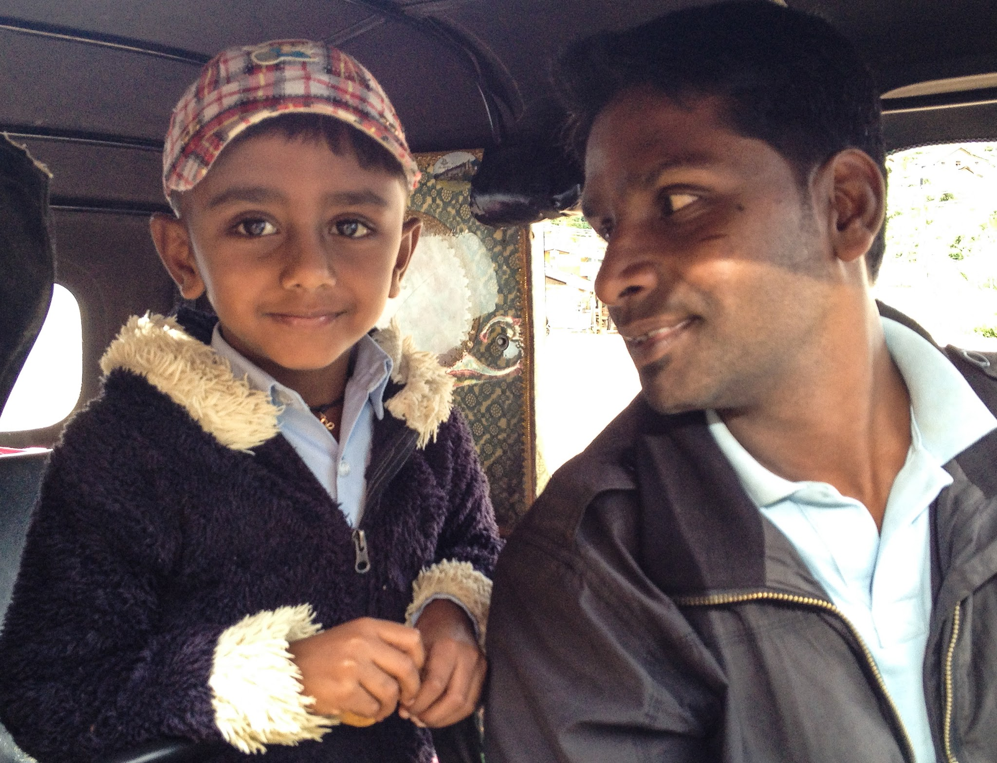 sri lankan tuk tuk driver and his son on their way to school