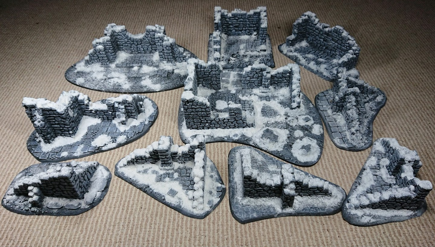 Collection of ruins, painted grey with snow effects laid out on a carpeted floor.