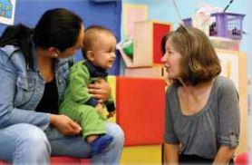 Two caregivers smiling and talking to an infant. One of them is holding the infant on her knee.