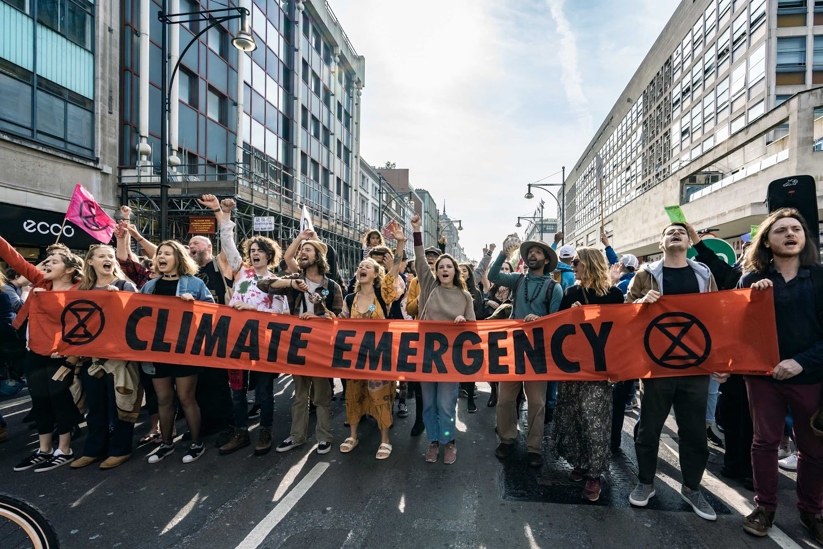 "Rebels blocking a street, holding a ""Climate Emergency"" banner."
