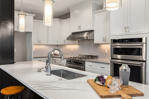 Benefits of Quartz Countertops; white kitchen countertop with white cabinets in the background