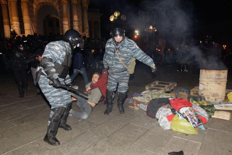 «Беркутовцы» тащат студента-протестующего во время ночного разгона студенческой акции протеста на Майдане Независимости, 30 ноября 2013 года