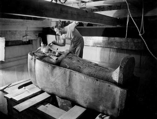 Image - Discovery of the tomb of pharaoh Tutankhamun in the Valley of the Kings (Egypt) : in burial chamber, Howard Carter working on the lid of the second coffin, october 1925, photo by Harry Burton (p1568), © Tallandier / Bridgeman Images