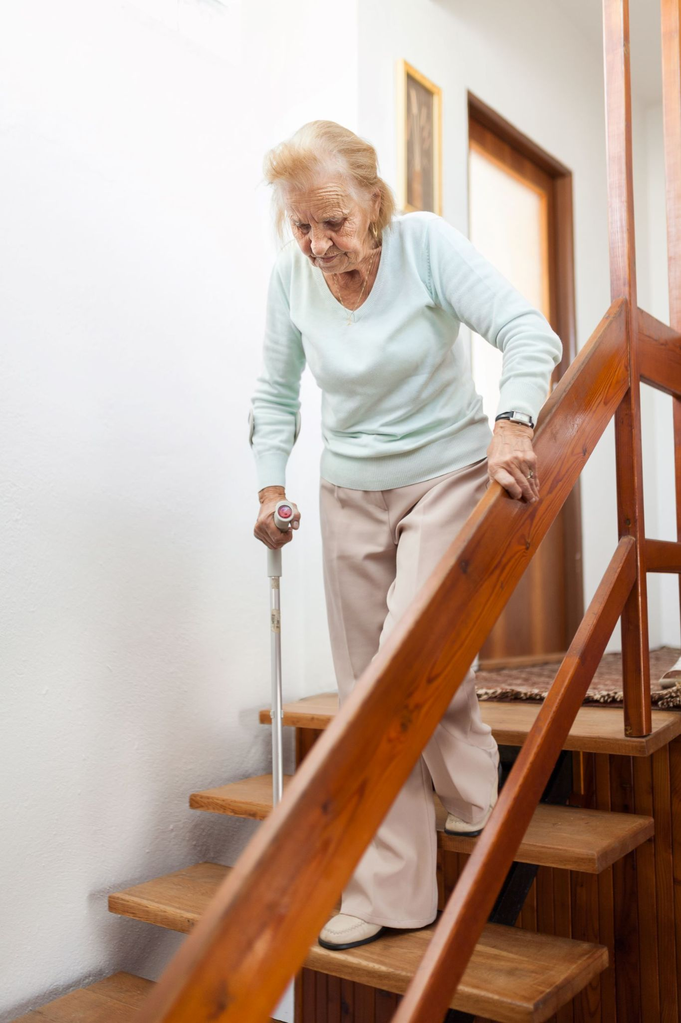 older-woman-using-cane-to-walk-down-staircase