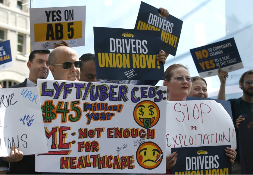 """Protesters hold up signs like """"Yes on AB5"""", """"Drivers union now!"""", """"Stop the Exploitation!"""", and call-out tech company CEO's that make millions of dollars per year."""