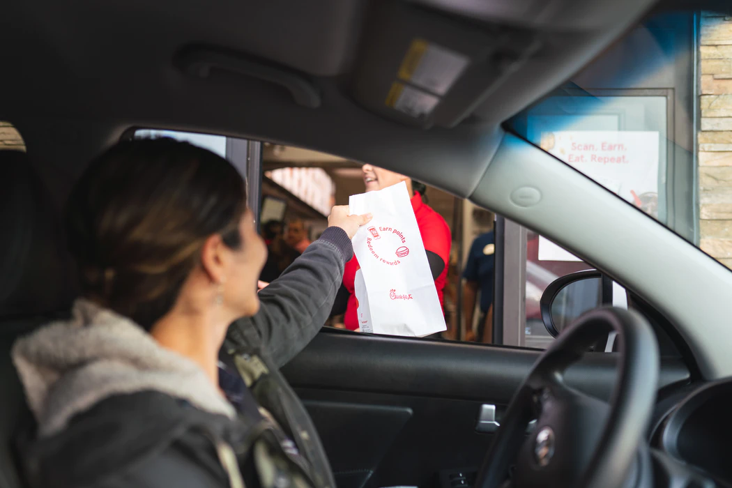 A person at a drive through window receiving a bag of food