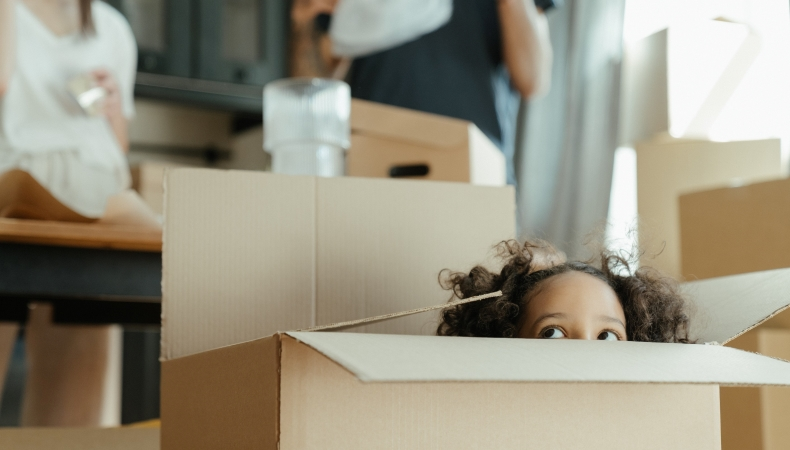 little girl peeking out of a moving box