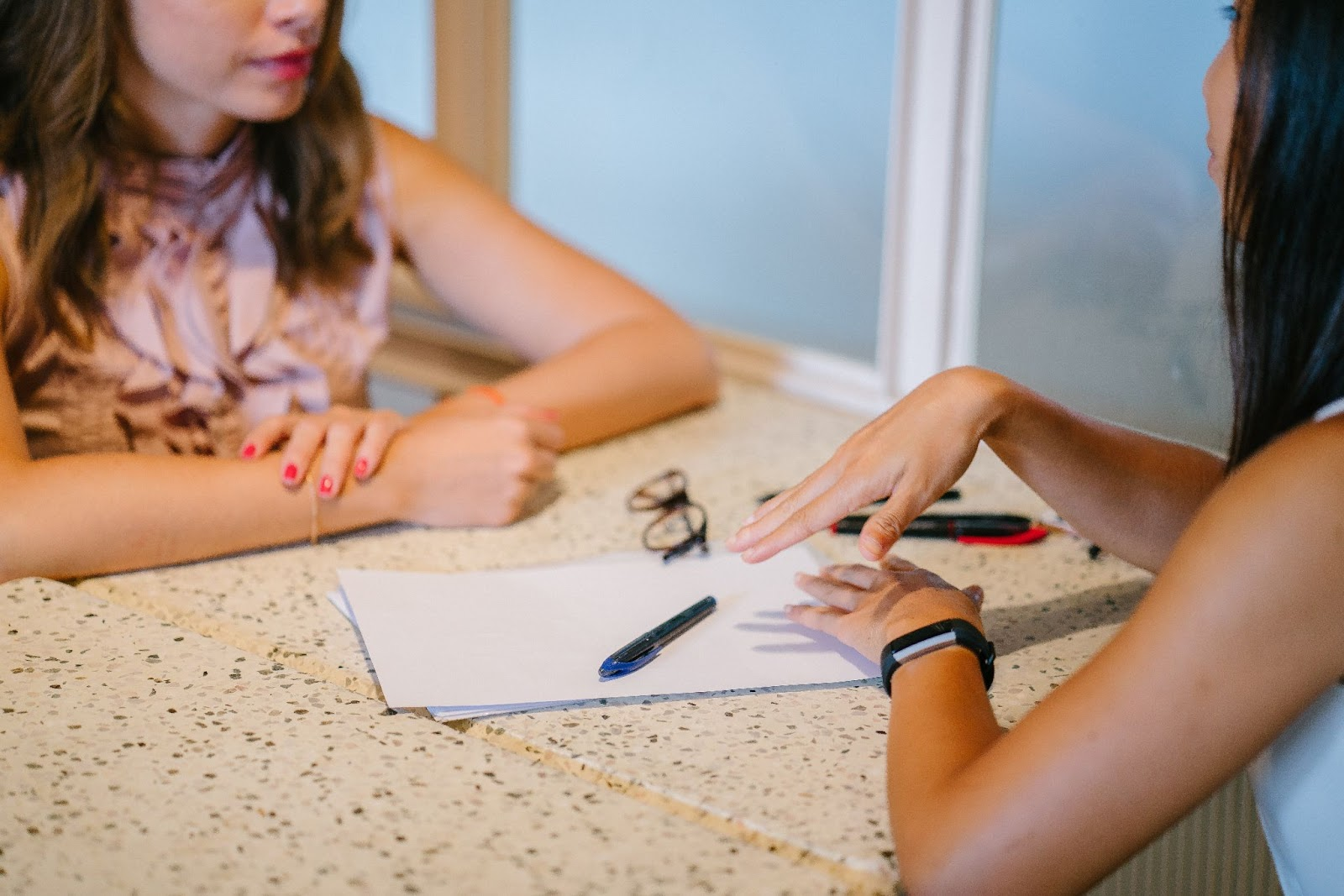 Women talking with a resume on the table How to Write a Great Resume
