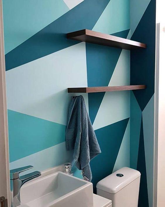 Banheiro com parede pintada com formas geométricas em tons de azul