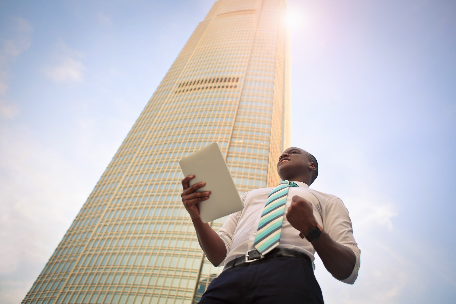 Um homem com um tablet na mão comemorando em frente de um prédio.