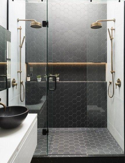 banheiro moderno com revestimento hexagonal preto na parede e piso, chuveiros dourados, bancada branca com cuba preta e torneira dourada.