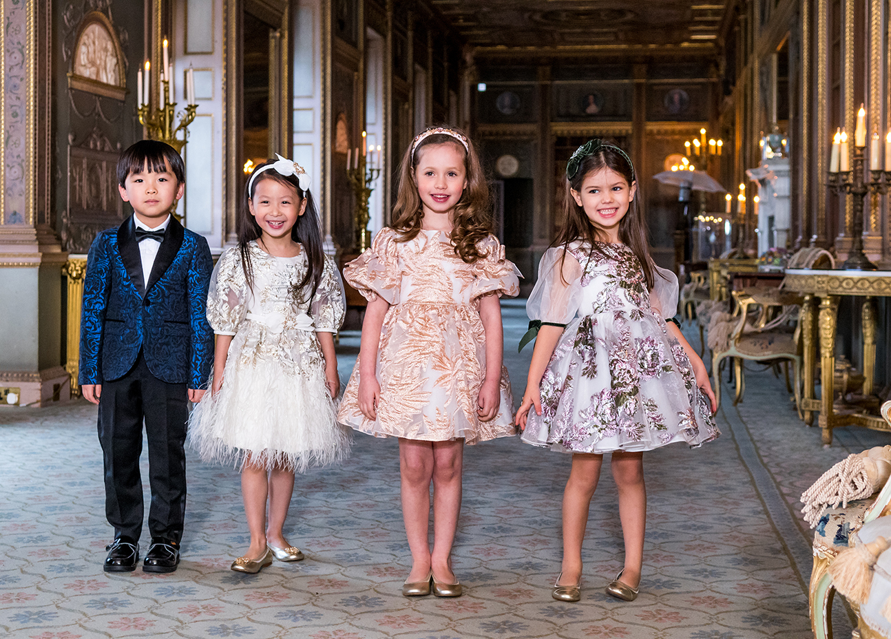 one boy and three girls wearing luxury designer childrens wear in a fancy building.