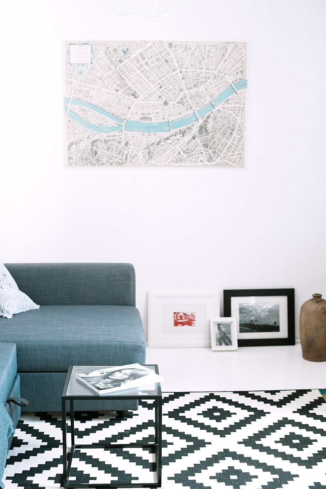 condo interior design with a map sketch hung on the white wall and blue couch and white and black pattered carpet on the floor of a condo unit