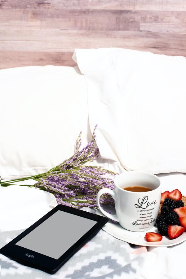 foto da cama com flores lavandas, chá, frutas e um kindle