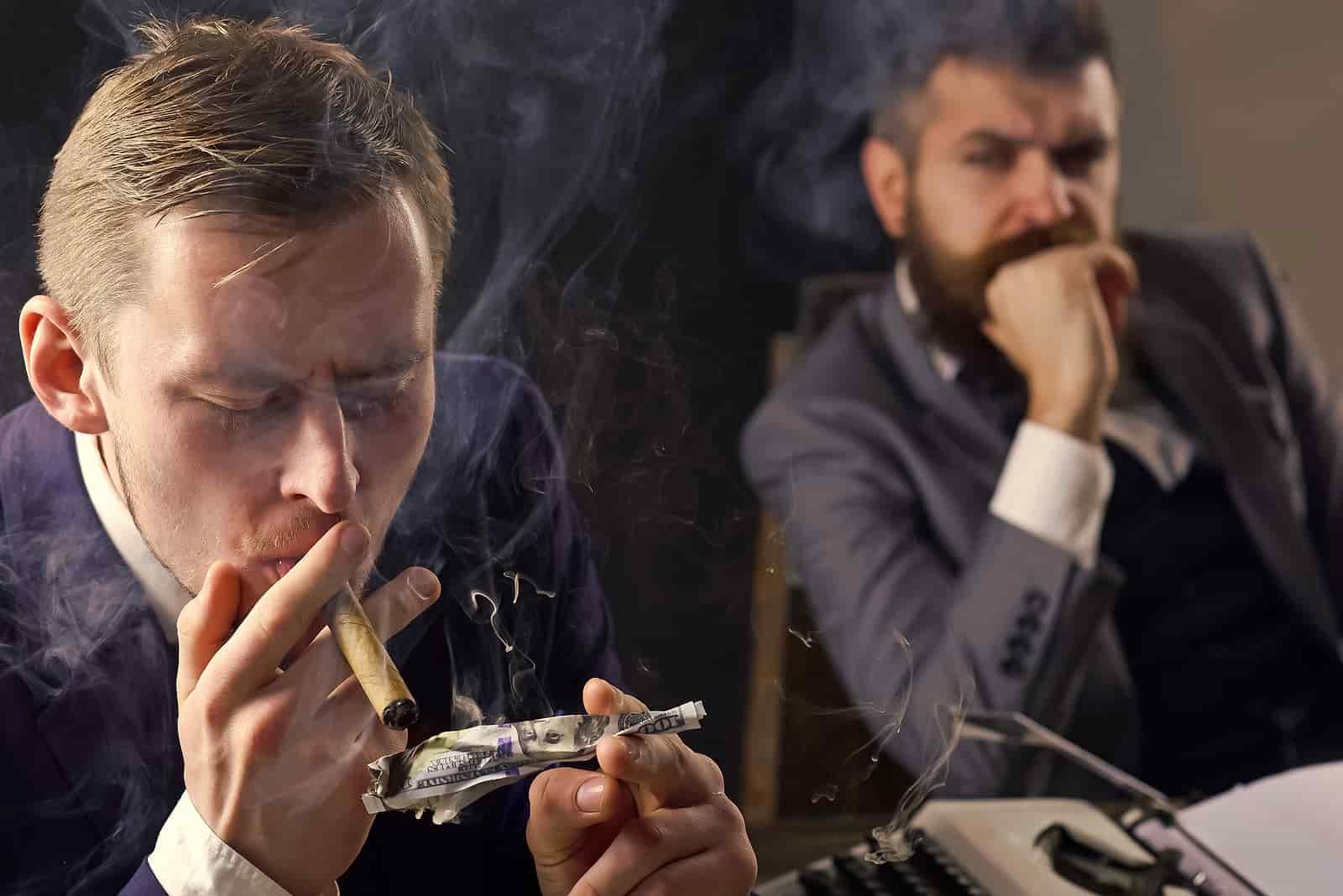 homem queimando dinheiro para fumar um cigarro